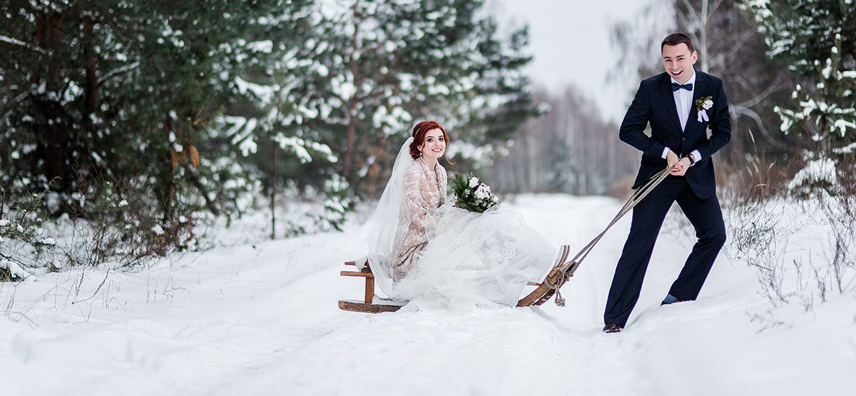 groom pulling his bride on a sled